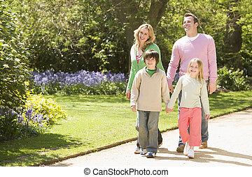 familia caminar, en, trayectoria, manos de valor en cartera, sonriente