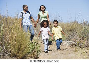 familia caminar, en, trayectoria, manos de valor en cartera, y, sonriente