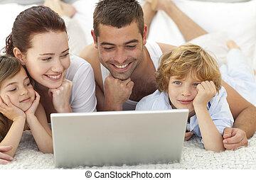 familia , en cama, juego, con, un, computador portatil