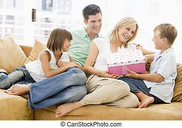 familia , en, sala, con, madre, receiving, regalo, y, sonriente