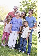 familia extendida, posición, en el estacionamiento, manos de valor en cartera, y, sonriente