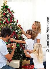 familia feliz, árbol de navidad decorando
