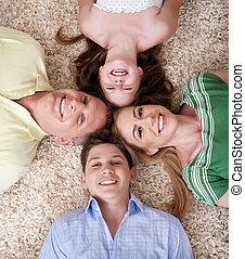 familia feliz, acostado, con, su, cabezas, muy cerca, sonriente