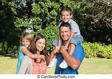 familia feliz, con, niños, en, su, hombros