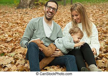 familia feliz, el sentarse en el parque