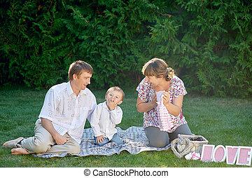 familia feliz, el sentarse en la hierba, en, un, parque, con, cartas, amor