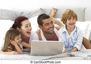 familia feliz, en cama, utilizar, un, computador portatil