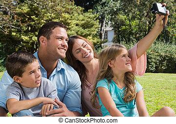 familia feliz, en, un, parque, tomar las fotos