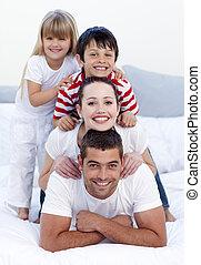 familia feliz, juego, en cama, juntos