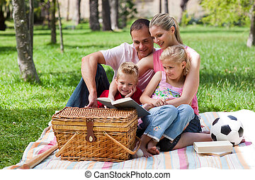 familia feliz, lectura, en, un, parque