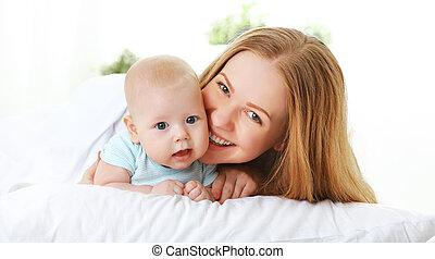 familia feliz, madre, con, bebé, en cama
