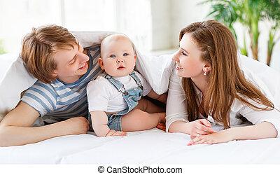 familia feliz, madre, padre, y, bebé, en cama