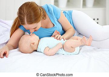 familia feliz, madre que juega, con, bebé, en cama