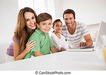 familia feliz, mirar la cámara, con, un, computador portatil