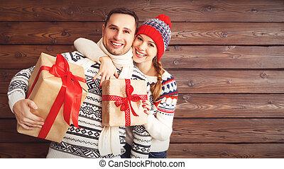 familia feliz, pareja, con, regalos de navidad, en, de madera, plano de fondo