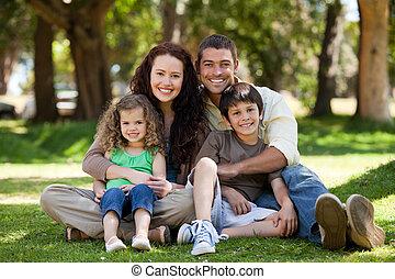 familia feliz, sentado, en el jardín