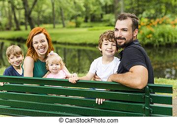familia feliz, sentar banco, en el estacionamiento