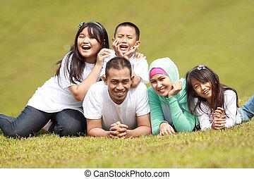 familia feliz, sonriente, en el parque