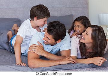 familia feliz, tener diversión, en la cama