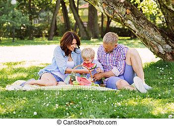 familia feliz, tener un picnic, en el parque, comida, un, sandía