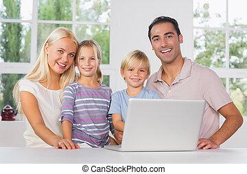familia feliz, utilizar, un, computador portatil, juntos