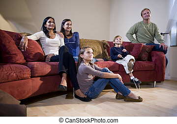 familia interracial, sentado, en, sala, sofá, mirando tele