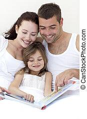familia joven, lectura, en cama