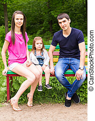 familia joven, mamá, papá, hija, sentado, en, un, banco, en, verano, parque
