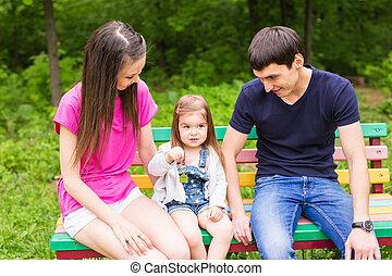 familia joven, sentado, en, un, banco, en, el, verano, parque