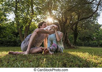 familia joven, sentado, en, un, pasto o césped, en el estacionamiento