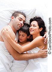 familia joven, sueño, en cama