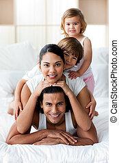 familia joven, tener diversión, en la cama