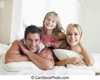 familia , mentira en cama, sonriente