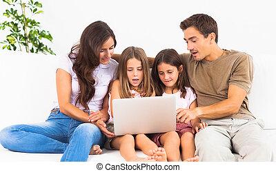 familia que coloca, en, un, sofá, con, el, computador portatil