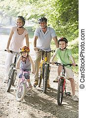 familia , sentado, en, bicicletas, en, trayectoria, sonriente