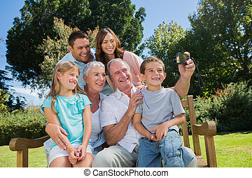 familia , sentado, en, un, banco, cautivadora foto, de, ellos mismos