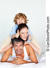 familia , tener diversión, en cama, con, pulgares arriba