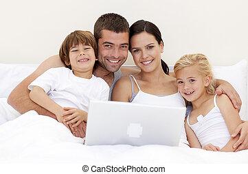 familia , usar la computadora portátil, en cama