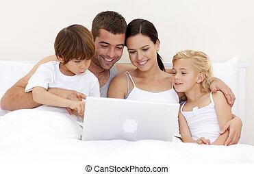 familia , utilizar, un, computador portatil, en cama