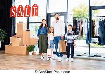 familie, mit, einkaufstüten, in, kleiderladen