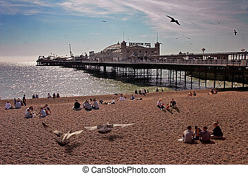 Families relax at the seaside beside Brighton Pier in Sussex England.