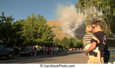 families watch forest fire burning near neighborhood