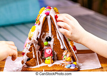 Familiy building a sweet ginger bread house