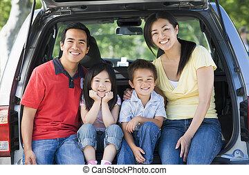 familj, sittande, i rygg av, skåpbil, le