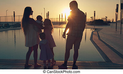 famille heureuse, à, trois enfants, admirer, les, coucher soleil, reflété dans, les, surface, de, les, piscine