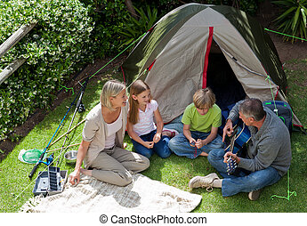 famille heureuse, camping, dans jardin