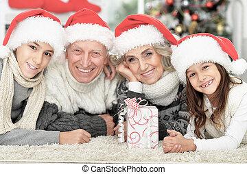 famille heureuse, chapeaux, santa, plancher, cadeau
