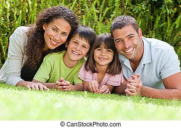 famille heureuse, coucher, dans jardin