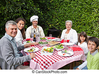 famille heureuse, manger, dans jardin