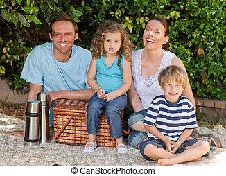 famille heureuse, pique-niquer, dans jardin